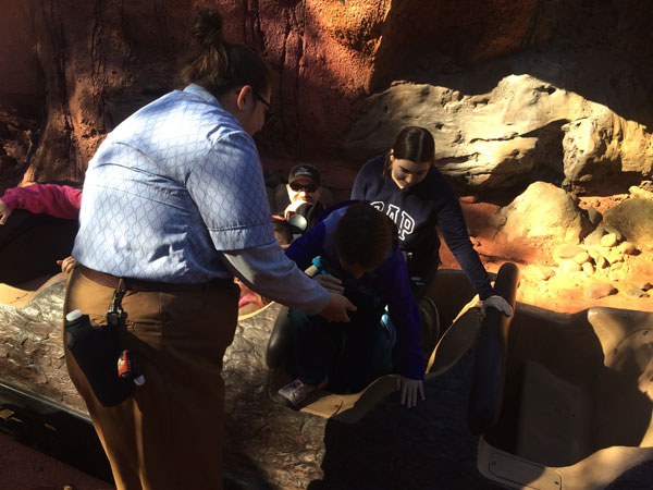 A cast member helps my wife and child out of their log and onto the emergency exit path.