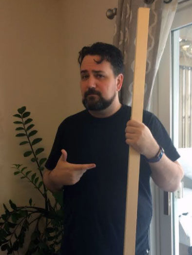 Ryan Henson Creighton, a bearded man in his 40's wearing a black t-shirt and a purple Fitbit, stands between a fern and a sliding glass door holding a piece of wood and pointing to it.