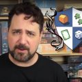 Ryan Henson Creighton makes board game videos for his YouTube channel, Nights Around a Table. Image depicts Ryan, a bearded man in his 40's, standing in front of a shelf full of various board games, next to the blue and white shield logo for Nights Around a Table