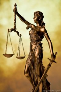 the scales of justice - a brassy statuette of a blindfolded lady justice with a sword and a set of balance scales, set against an artsy brown and yellow background
